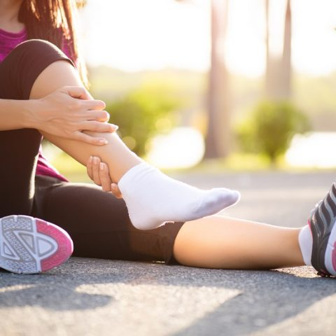 Ankle sprained. Young woman suffering from an ankle injury while