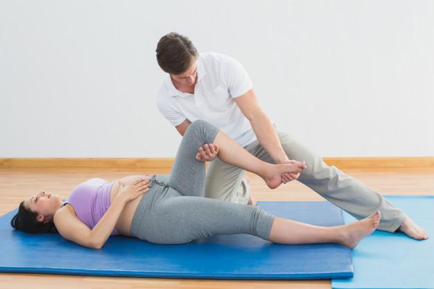 masseur-moving-pregnant-womans-leg-blue-mat_13339-71936